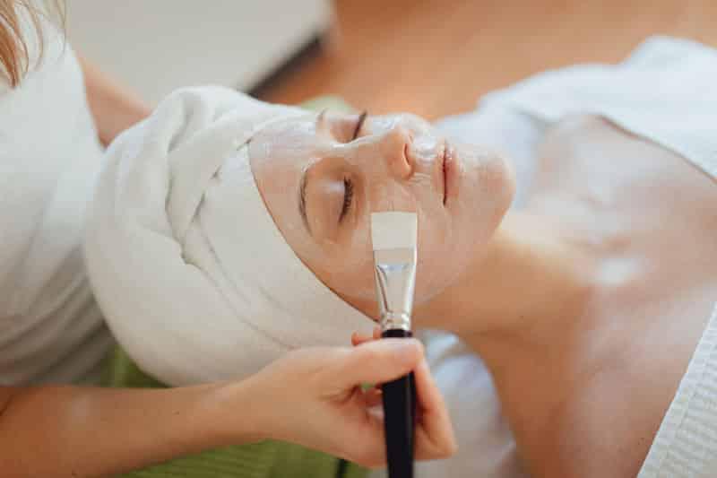 Eine Maske wird mit einem Pinsel bei einer Frau aufgetragen