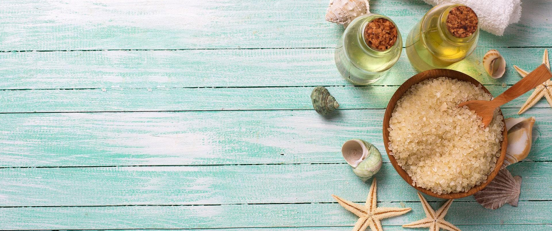 Sommerbehandlung, Muscheln, Seesterne, Salze und Öl auf einem türkisen Tisch